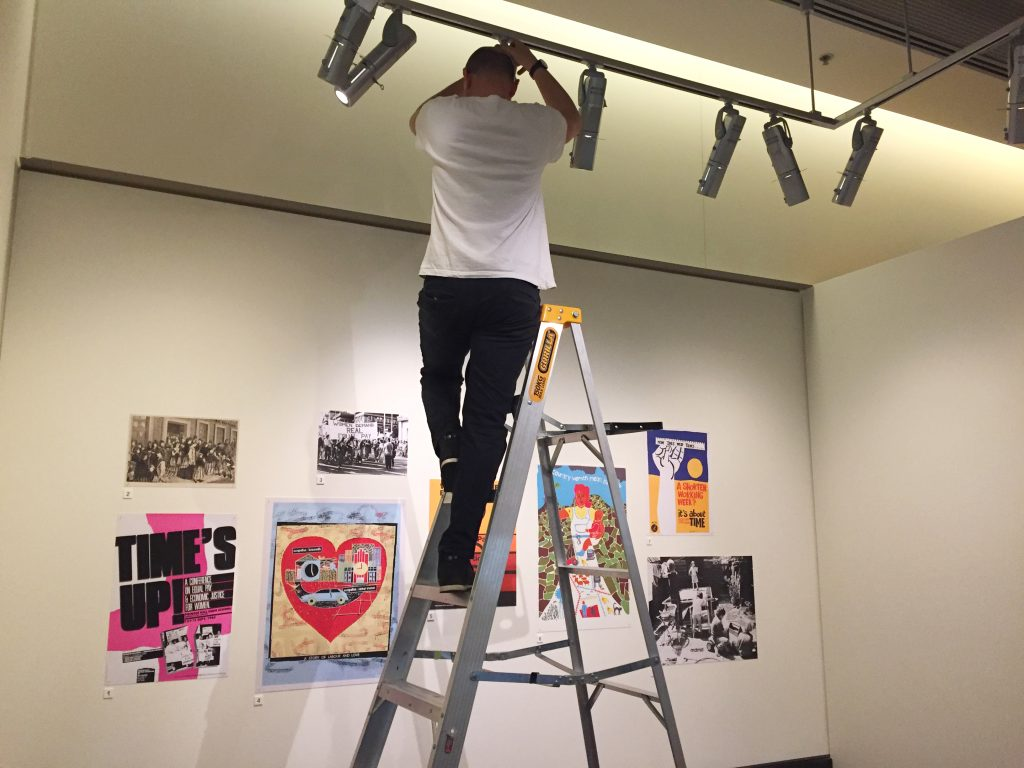 Man on a ladder adjusting the lighting of a group of posters during installation