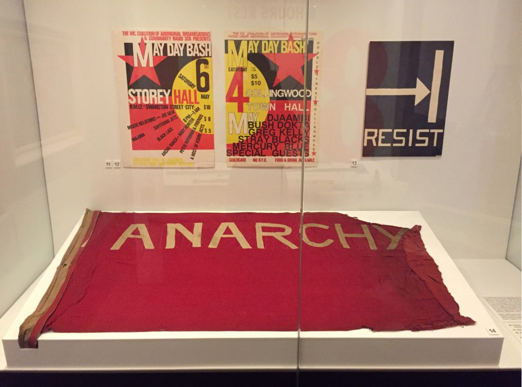 View of a showcase featuring Anarchy flag, a large red flag, installed on an angled plinth with three posters on the wall behind