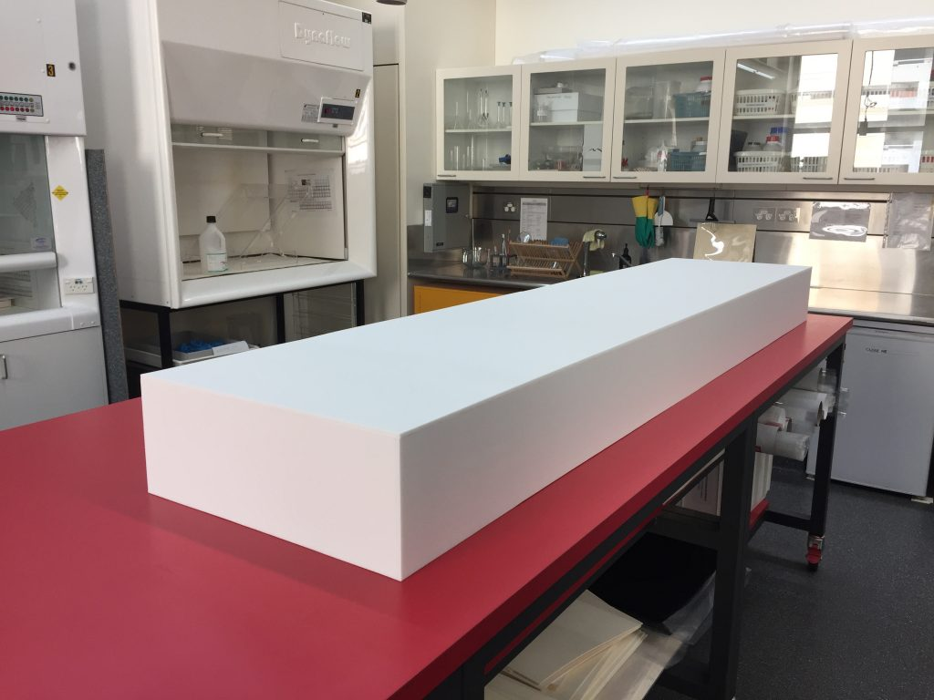 Long, rectangular, white plinth sitting on a red bench in the Conservation Lab