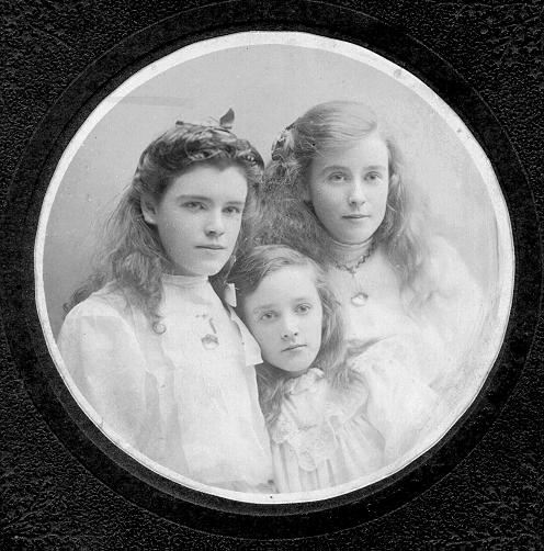 Black & white photograph of three young sisters with long hair wearing white blouses in circular mount.