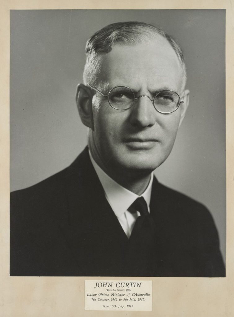 Black & white portrait of former prime minister John Curtin, wearing round spectacles, black suit jacket and tie.