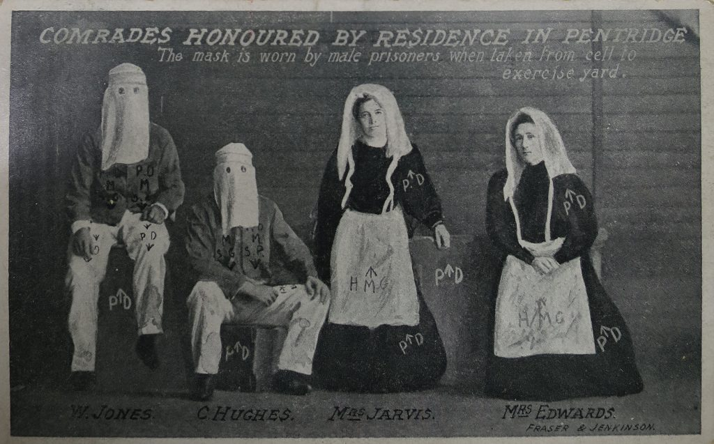 Black & white postcard of two men and two women in prison uniforms.