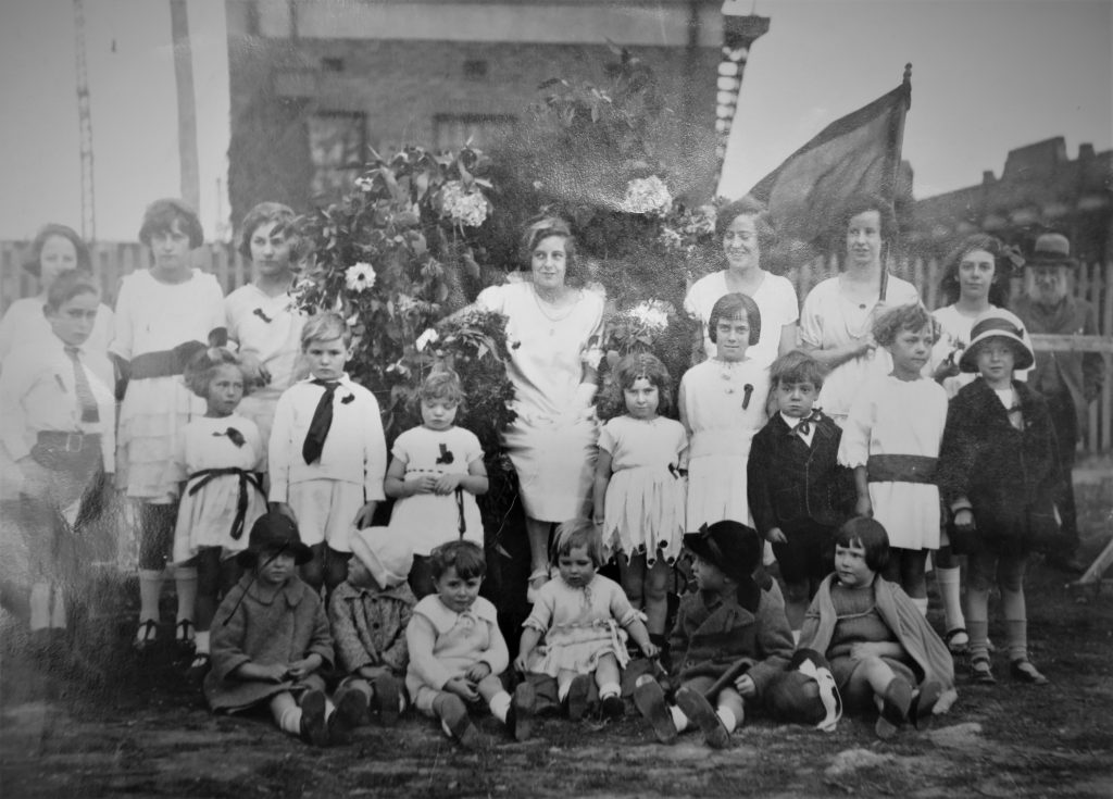 Black & white photograph of children and young women assembled under flower garland and flag.