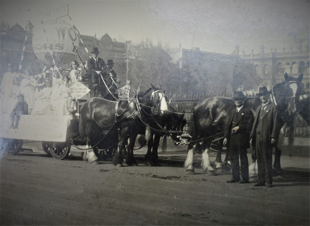 Black & white photograph of horse-drawn cart carrying men, women and children, with float decorated for May Day parade.
