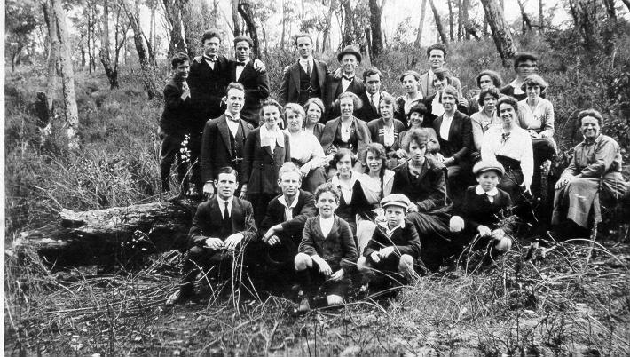 Black & white photograph of group of women and men in bushland.