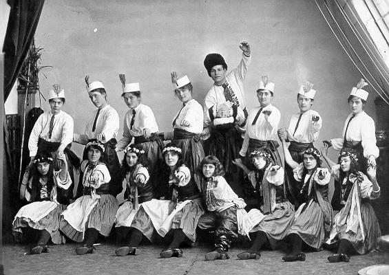 Black & white photograph of young women and men dressed in dancing costumes, posing with arms and legs outstretched.