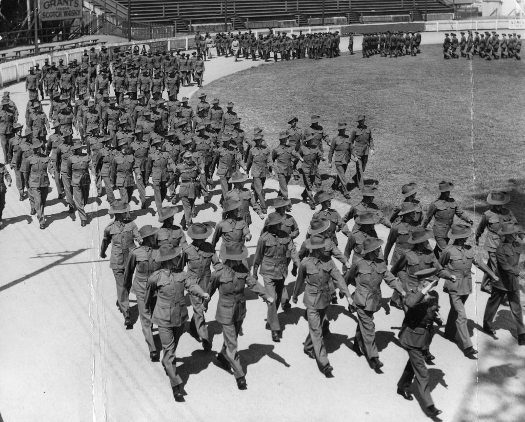 Black and white photo of Australian soldiers marching around racecourse in uniform
