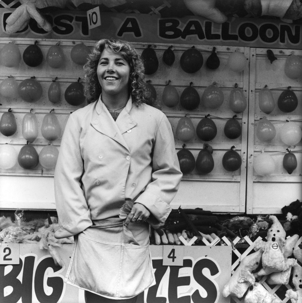 Black and white photo of a young woman standing in front of her sideshow, Bust a Balloon. She is holding darts in her left hand, and laughing at the camera