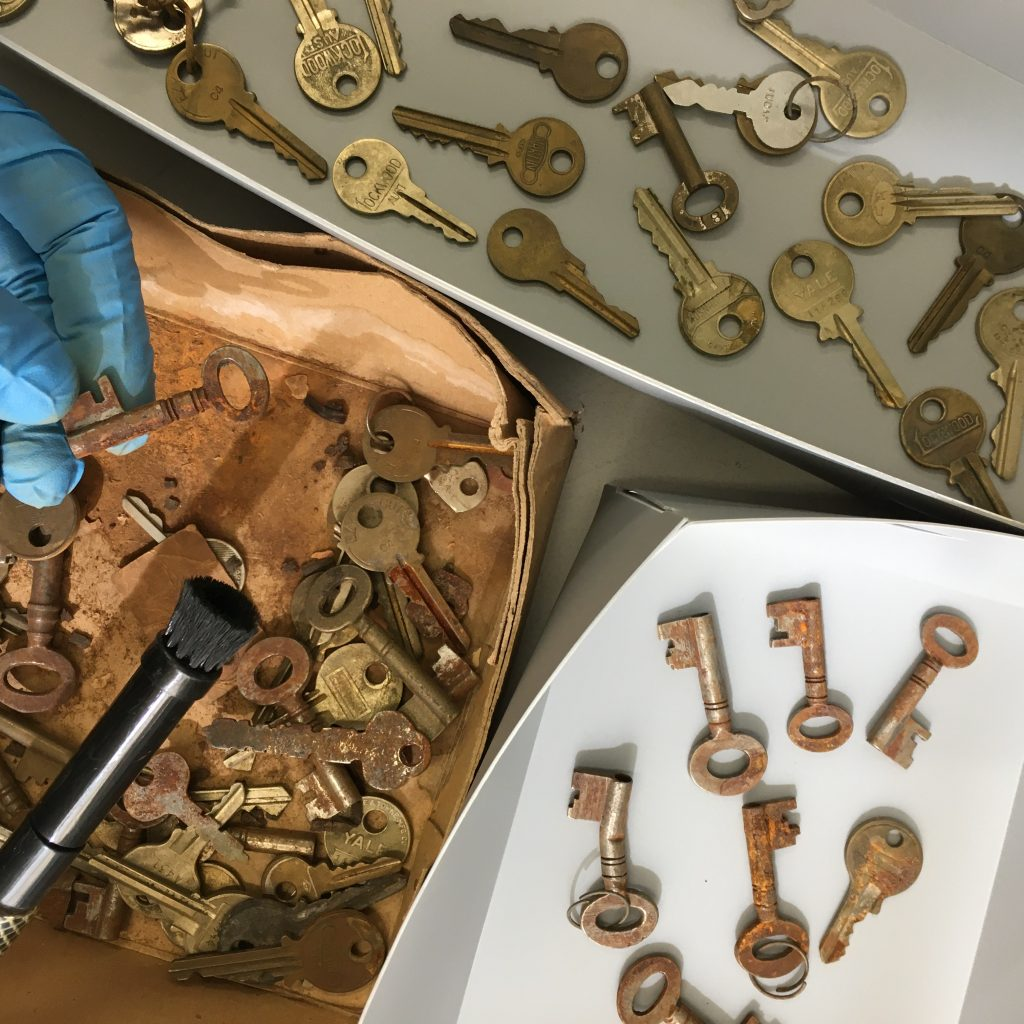 Photograph of keys being sorted, cleaned and rehoused by Preservation staff member