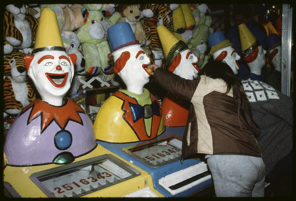 Colour photo of young girl playing laughing clowns game in Sideshow Alley