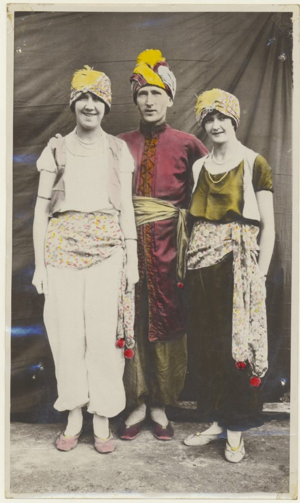 Three figures, whole length, in stylised middle-eastern dress, Len Morgan in centre between two women