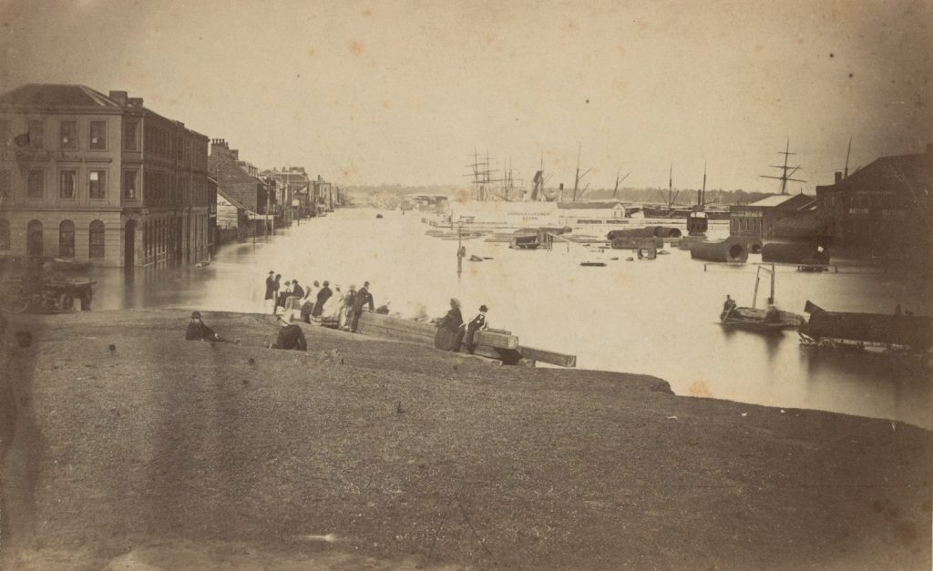 Black and white photo of the corner of Flinders and Spencer streets under flood in 1863