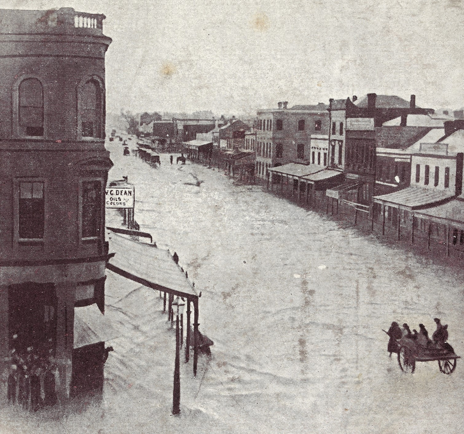 Black and white photo shows elevated view of Elizabeth Street, showing floodwater covering lower windows of buildings and posts of porches, horse and cart being driven through floodwater.