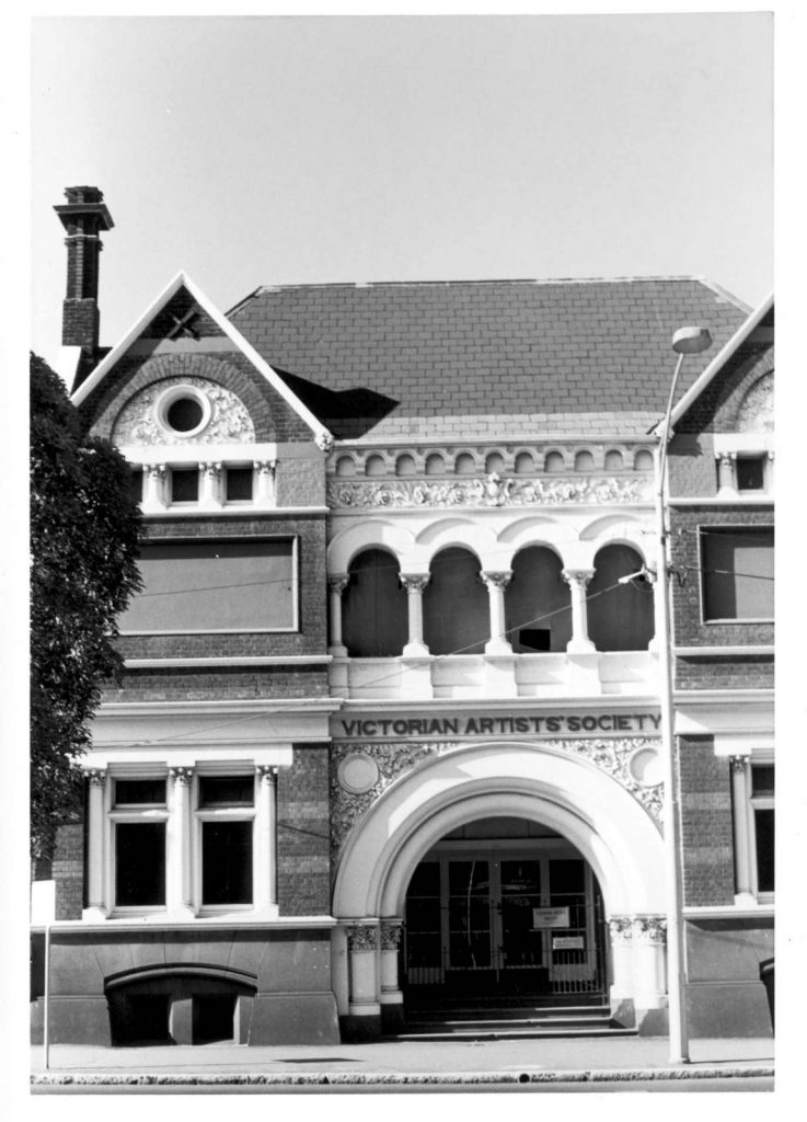 Black and white photo of double-storey building with arched doorway. Sign over archway reads 'Victorian Artists' Society'