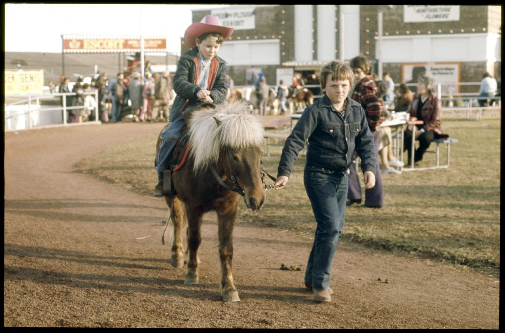 Young boy wearing a cowboy hat, sitting on a shetland pony being led around by an older boy.