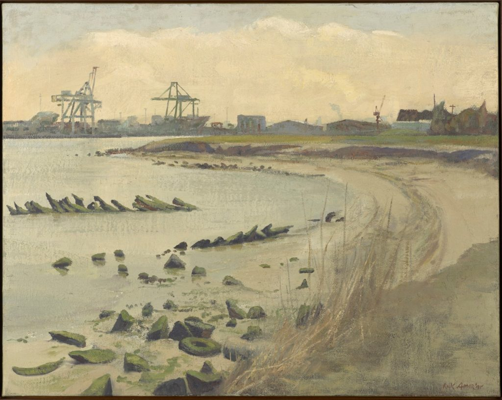 river with sandy beach, rocks and boat hull in foreground industrial background
