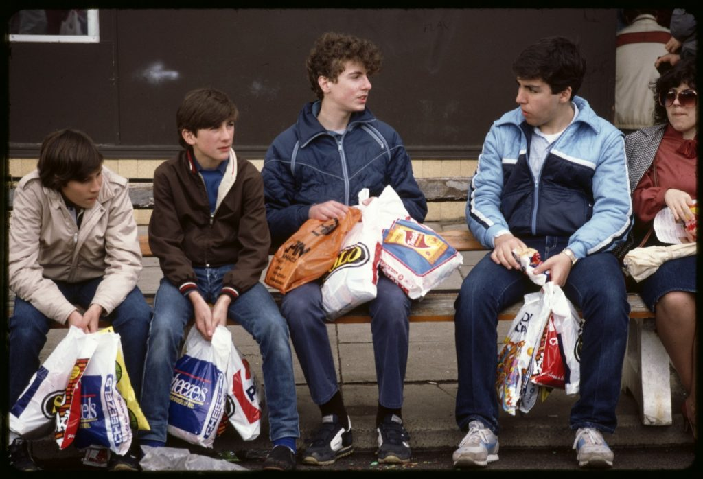 A group of four teenage boys sit on a bench holding several show bags each