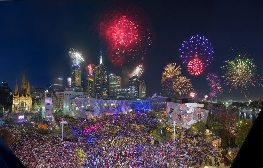 Fireworks above a large crowd at Federation Square
