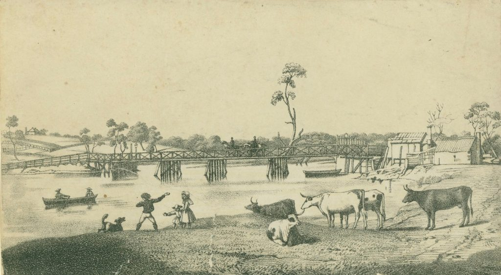 Wooden bridge crossing the river with people in a boat, cows, people and some buildings on the river bank.