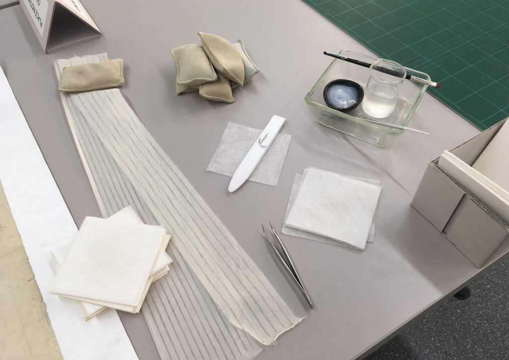 Tools and materials, including paste, brushes, and paper, used by conservators to mend tears in paper