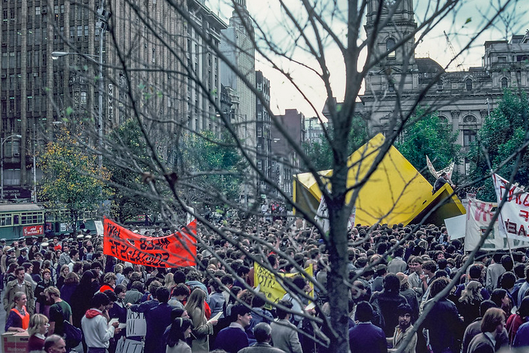 crowd at a rally, leafless tree in foreground and Vault, scuplture in the background