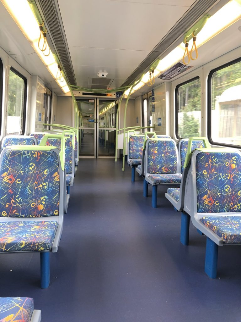 View of interior of train carriage, showing all seats unoccupied.
