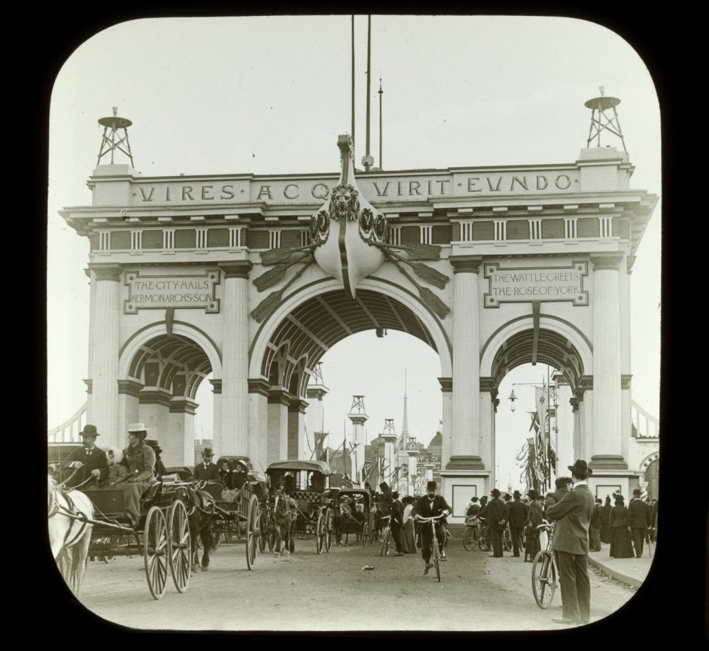 Carriages and cyclists travelling under the acrhes built at the end of Princes Bridge.