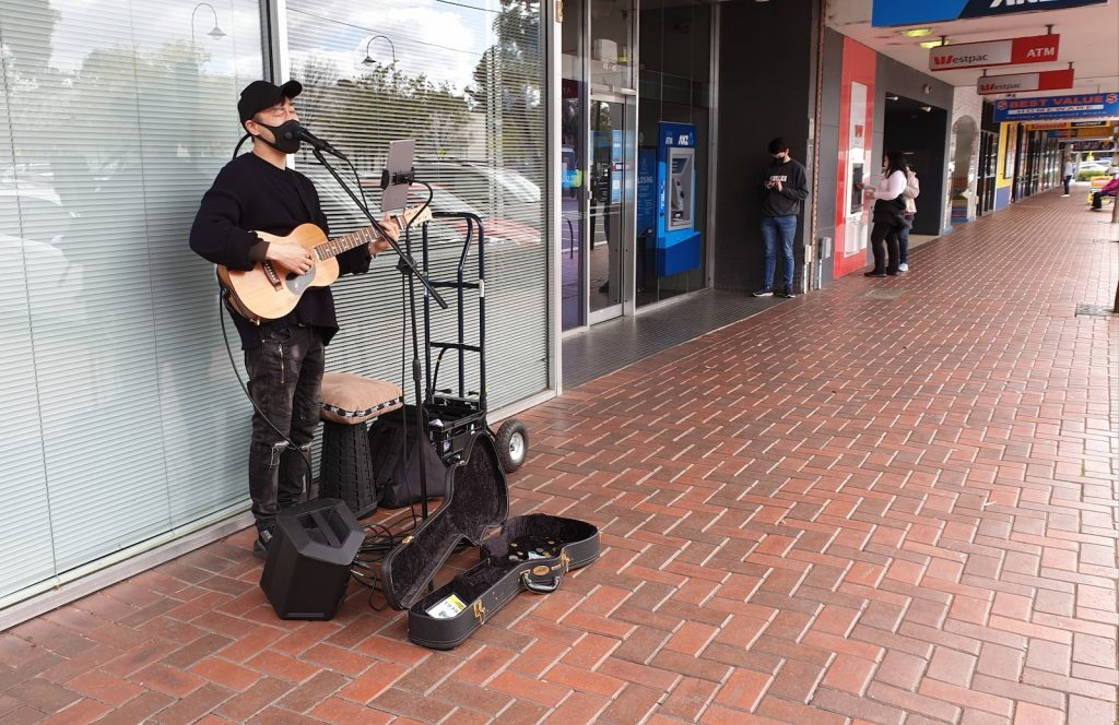Busker performing on the footpath, wearing all black, including his protective face mask.