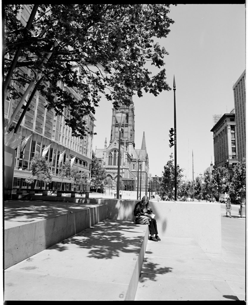 City Square with hotel building on the left, St Paul's Cathedral in the background, girl sitting reading in the foreground.
