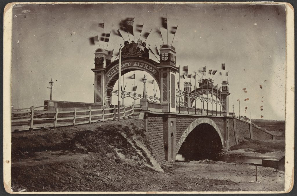 Decorated bridge with arches, and flags waving in the breeze.