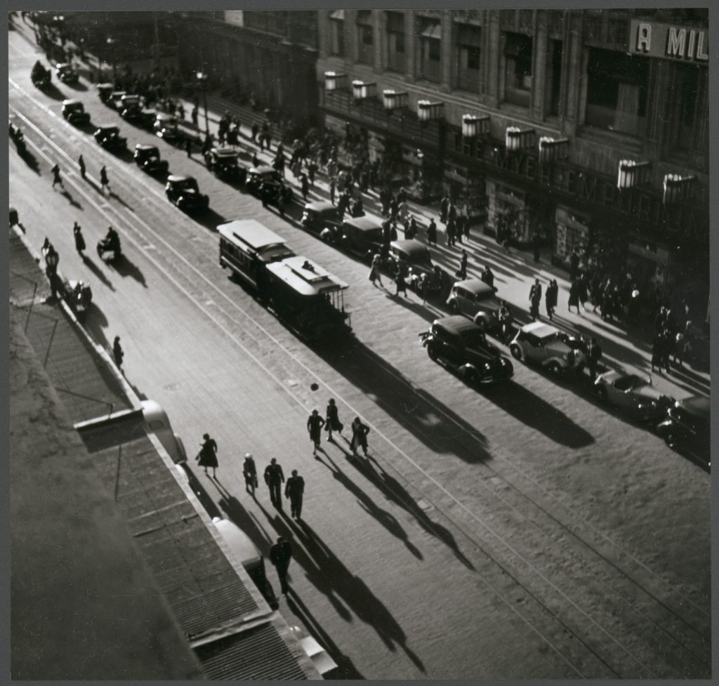 Aerial view of trams, cars and pedestrians forming shadows over the road.