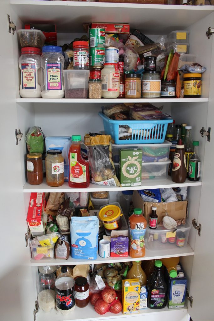 View of pantry shelves showing non perishable food and ingredients, and some vegetables.