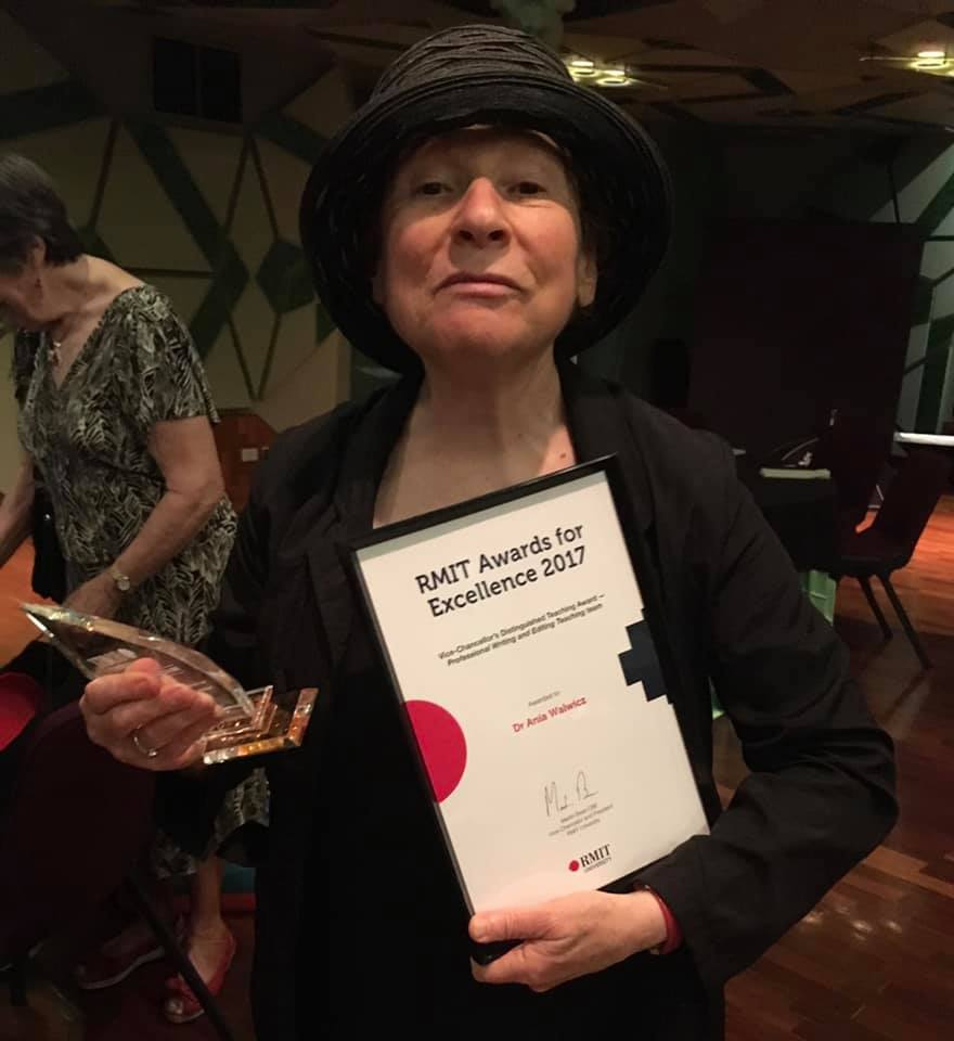 Photo of Ania Walwicz in a black hat, holding an award for excellence in teaching