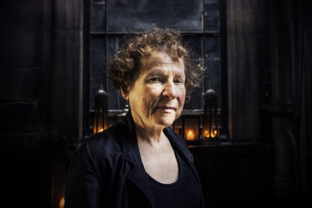 Photo of Ania Walwicz against a dark background. There are lit candles in the background