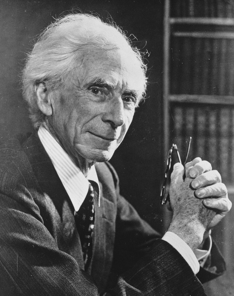 Black and white photo of Bertrand Russell holding reading glasses. There is a bookshelf behind him