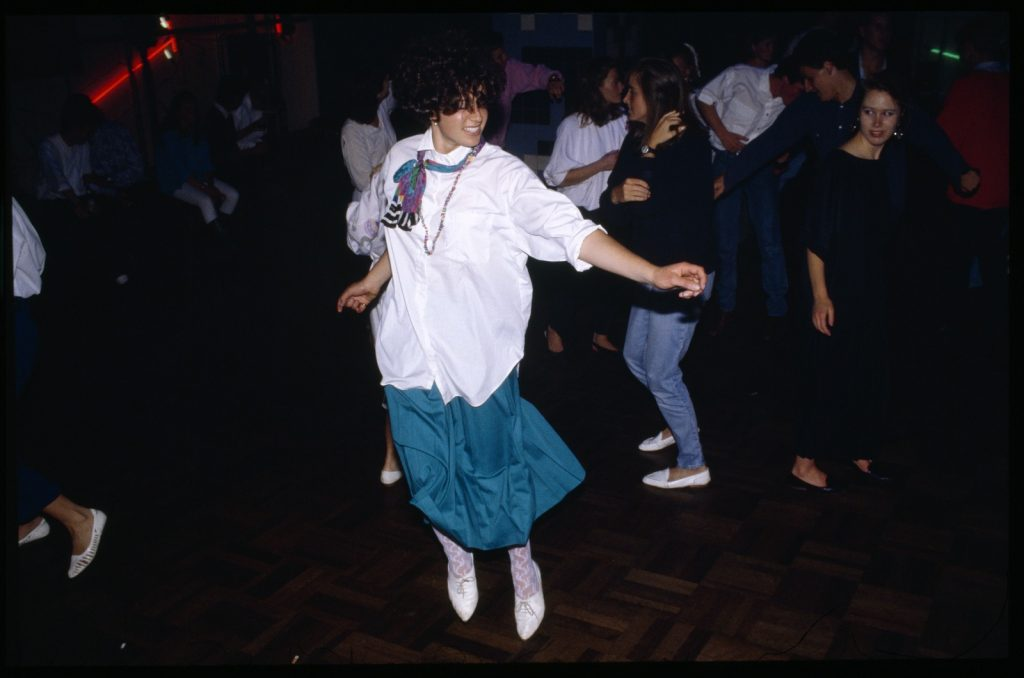 Woman wearing white shirt, multicoloured scarf, teal skirt, and white lacy hose, and white shotes, dancing enthusiastically at Inflation Nightclub