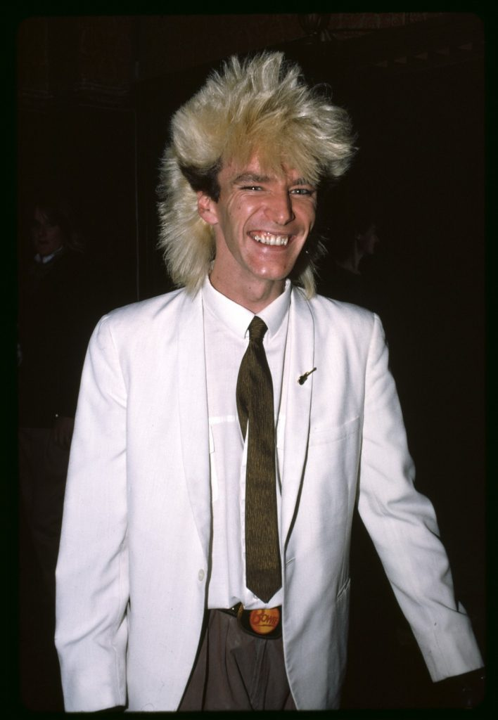 Smiling young man with dyed blond spiky hair with dark sides, wearing a white jacket with a golden guitar pin on his lapel, white shirt, skinny olive tie, tan pants with a Bowie belt buckle. Black background.