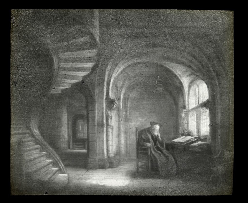 Black and white illustration of a philosopher sitting at a writing desk in a cave-like room. There is a winding staircase on his left