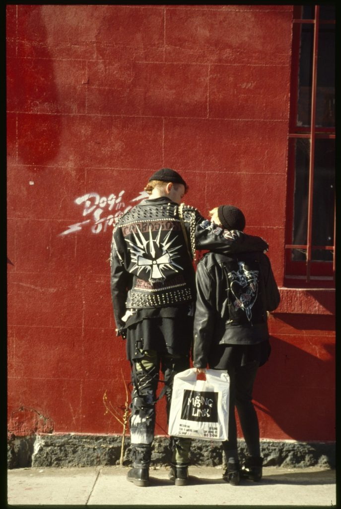 Black leather jacket clad and woolen beanie capped punk male and female in front of a red wall which has the Dogs in Space film logo stencilled onto it. Male and female with backs to the camera. Male has arm around female. Female carrying a Missing Link record bag. Male jacket has a 'Corrosion' logo with studs and a chain on shoulder. Female with heart and sword logo on jacket and black leggings.
