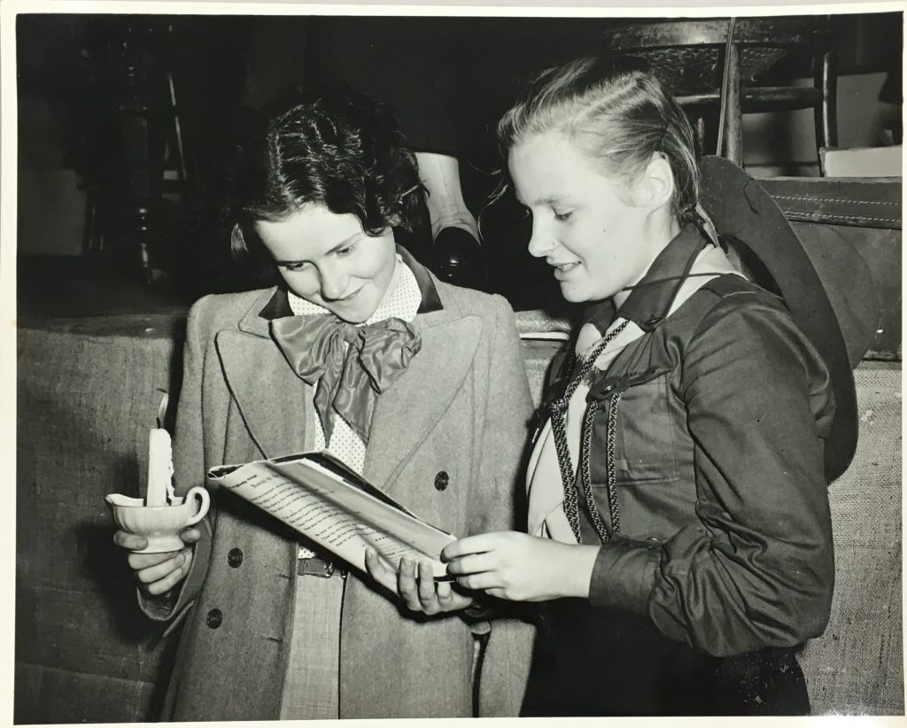 Two young women holding a candle and programme