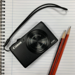 Digital camera sitting on top of notebook with pencil