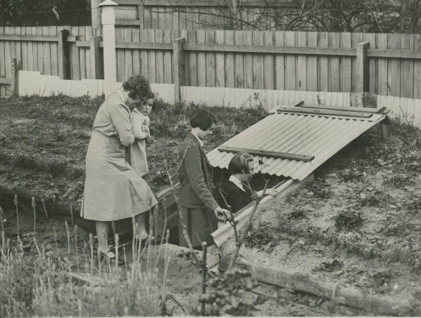 Shows family of women entering backyard air-raid shelter.