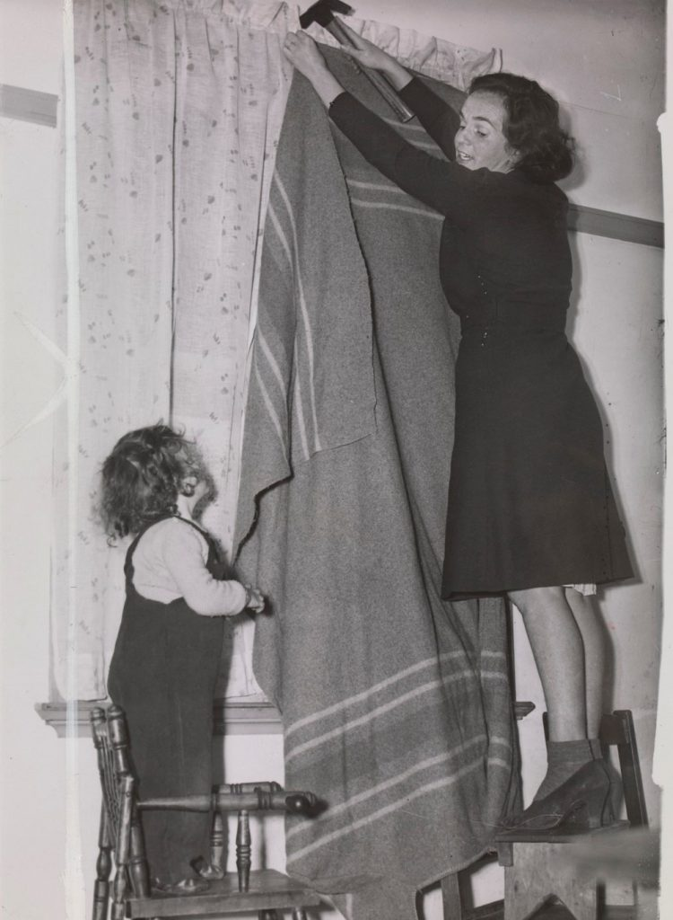 Shows woman on stool hammering a blanket over window, with small child watching; young patients of Prince Henry's hospital watch ward windows being prepared for blackout.