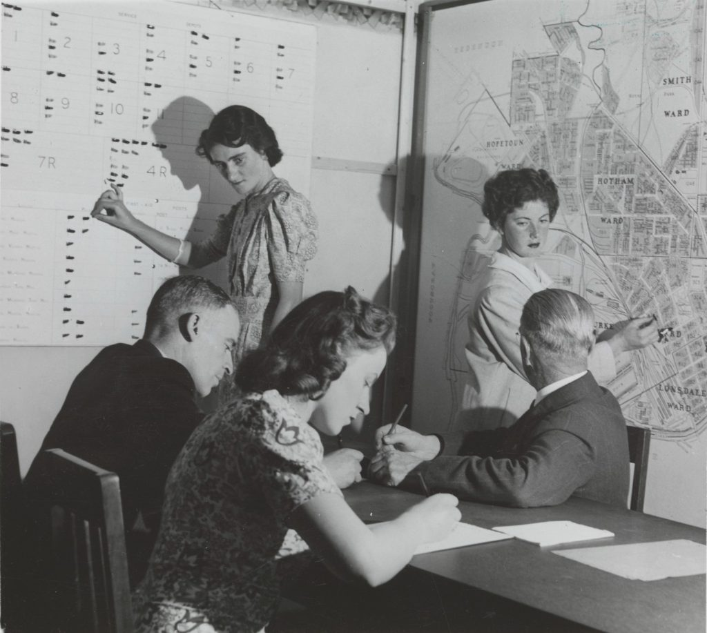 Shows man with open book in left hand, pointint at a map with his right hand; two men and a woman working at a desk in the foreground, two women making changes to chart and map fixed to the wall.