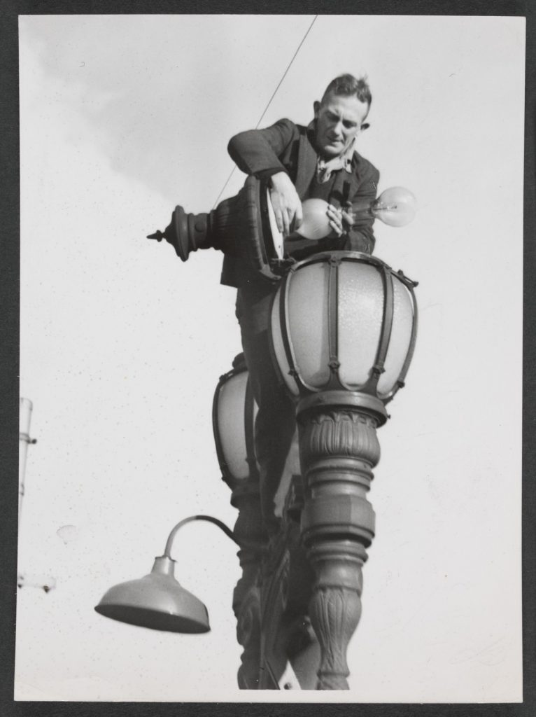 Shows council employee atop a light post, changing the light globes back to pre-brownout levels