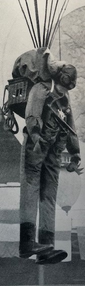 Uniformed soldier suspended from parachute with a basket of pigeons on his back