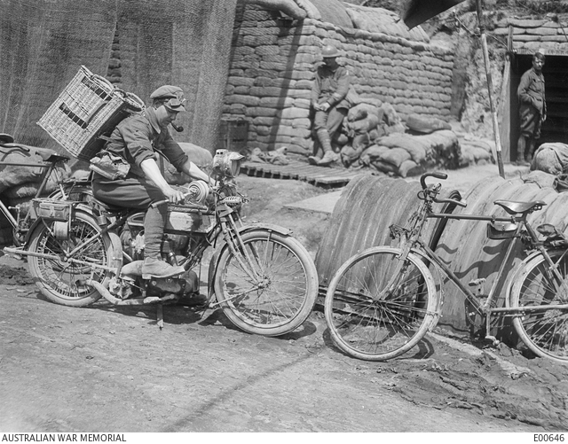 Black and white photo of a despatch rider leaving the signal office and headquarters of the 4th Australian Divisional Signalling Company at Vaulx, France, with a basket of carrier pigeons in 1917