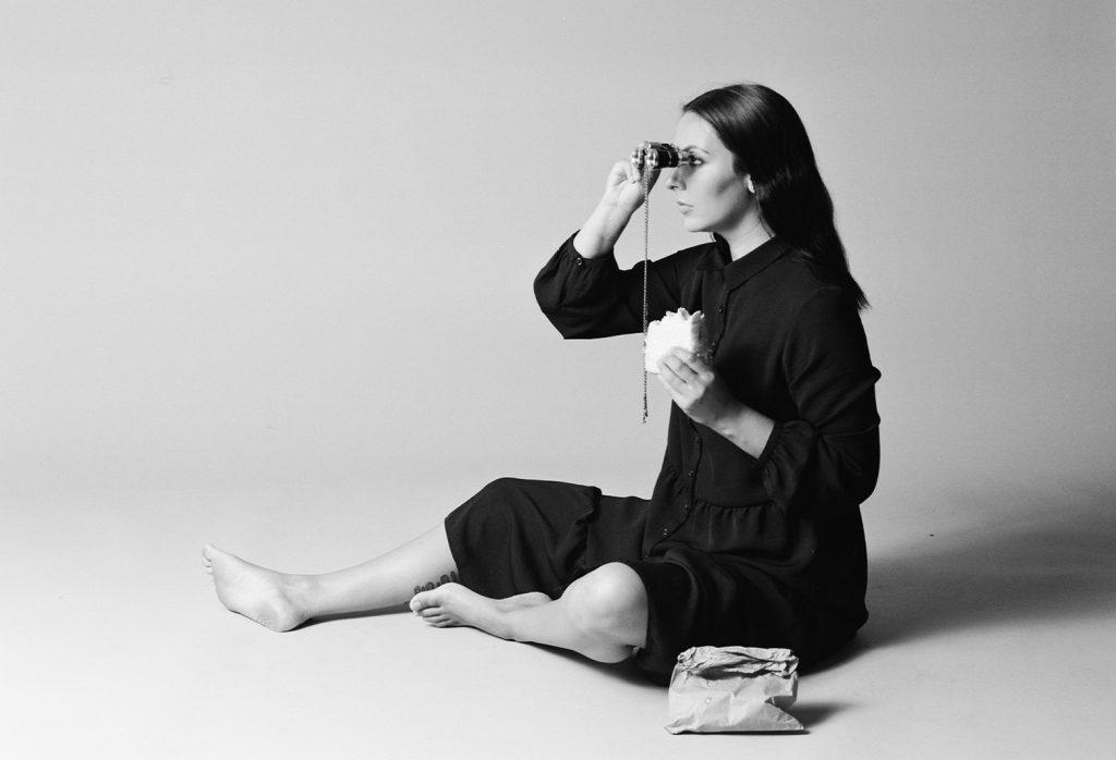 black and white photo of woman looking through binoculars