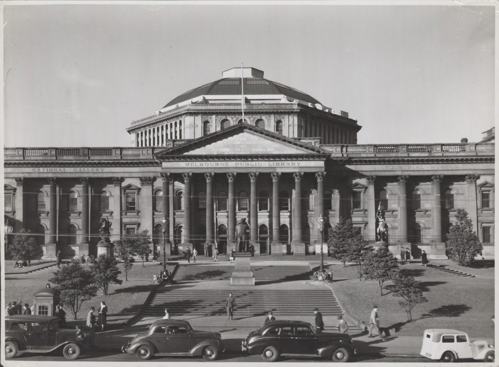 Slightly elevated view looking from Swanston Street towards the facade of the State Library of Victoria, railing fence between pillars of portico, showing lawns, steps leading up to forecourt, statues of Sir Redmond Barry, St. George and St. Joan of Arc. Public phone booth on path in left foreground. Cars parked in street in front of library. Lettering in architrave above pillars: National Gallery -- Melbourne Public Library -- Industrial Museum.
