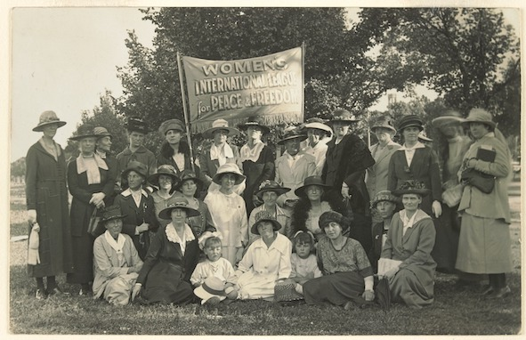 Photo of women and children outdoors, gathered around a sign reading 'Women's International League for Peace and Freedom'